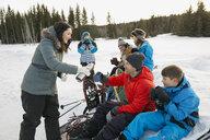 Multi-generation family taking a break from snowshoeing - HEROF00875