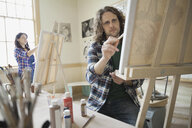 Man painting in art class using easel - HEROF00932