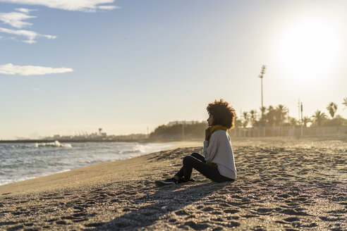 Woman sitting on the beach at sunset - AFVF02110