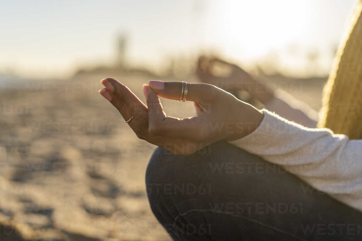Woman sitting on the beach at sunset, meditating - AFVF02116 - VITTA GALLERY/Westend61