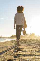 Barefoot woman on the beach, carrying her shoes - AFVF02119