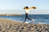 Woman running on the beach, wearing yellow scarf - AFVF02128