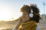 Woman with yellow scarf, listening music on the beach - AFVF02137