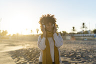 Woman with yellow scarf, listening music on the beach - AFVF02140