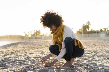 Woman collecting seashells on the beach - AFVF02143