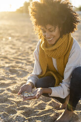Woman collecting seashells on the beach - AFVF02146