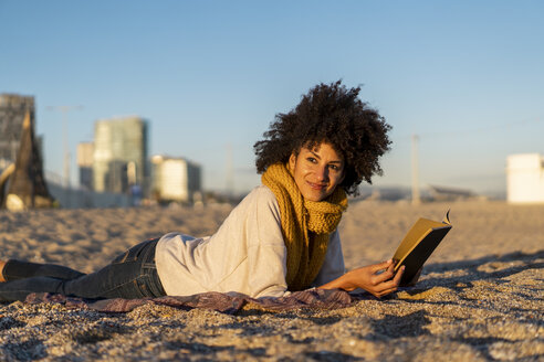 Woman lying in the sand, relaxing on the  beach, reading a book - AFVF02149