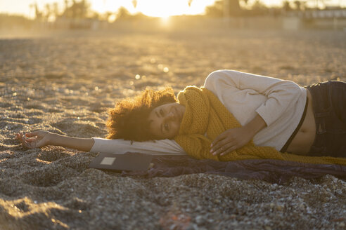 Woman lying in the sand, relaxing on the  beach - AFVF02152