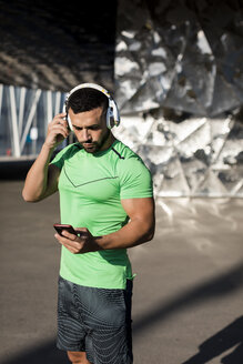 Sportive man during workout, using smartphone and headphones - MAUF01964