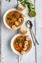 Two bowls of sweet potato soup with  shrimps, coconut flakes and fresh coriander - SARF04023
