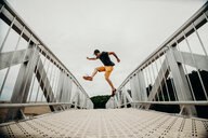 Action shot of a young man jumping in midair over an architectural bridge - INGF10409