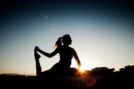 Silhouette of a woman stretching out in nature during sunset - INGF10421