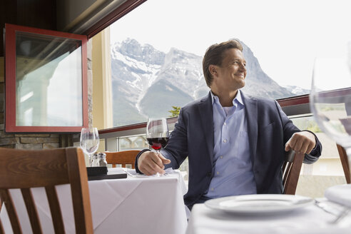 Businessman drinking wine at table on balcony - HEROF01201