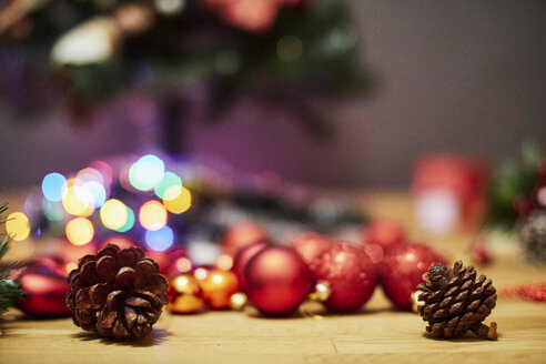 Fir cones and Christmas baubles on wooden floor - BZF00474