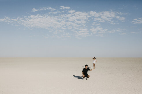 Man kneeling in the desert, with woman seeming to balance on his hand - LHPF00207