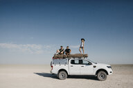 Friends on a safari, standing on their off-road vehicle - LHPF00213