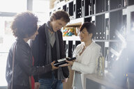 Sommelier recommending bottle to couple in wine store - HEROF01299