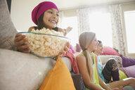 Smiling girl holding popcorn bowl at slumber party - HEROF01374