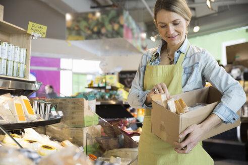 Worker stocking cheese in market - HEROF01422