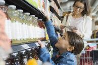 Girl reaching for juice on shelf in market - HEROF01476