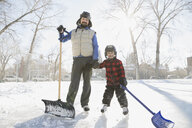 Portrait of father and son with snow shovels on ice rink - HEROF01524