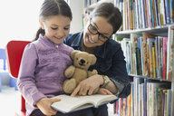 Mother and daughter reading book in bookstore - HEROF01659