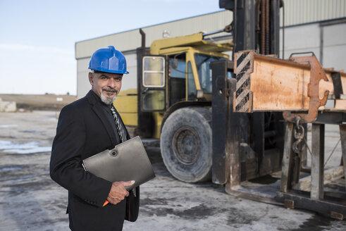 Portrait of confident businessman on industrial site near bulldozer - JASF02019