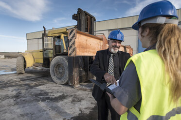Businessman talking with female worker on industrial site - JASF02025