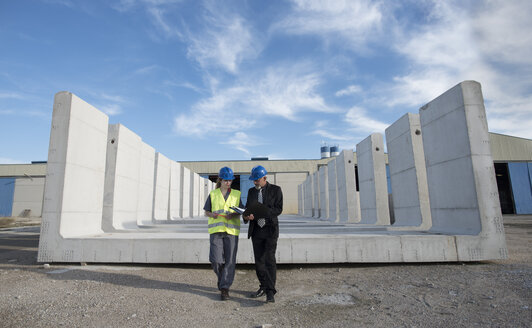 Businessman talking with female worker on industrial site in front of concrete blocks - JASF02028