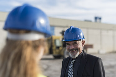 Portrait of businessman smiling at female worker on industrial site - JASF02034