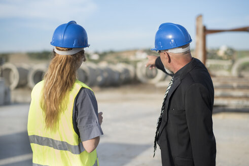 Businessman talking with female worker on industrial site - JASF02037