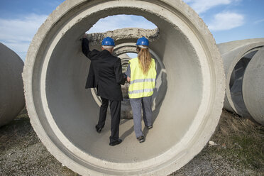 Businessman and female worker standing inside concrete pipe on industrial site - JASF02040