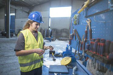 Woman working in factory adusting metal pieces - JASF02046