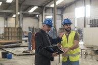 Businessman with folder talking to worker in factory - JASF02055
