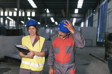 Male and female worker wearing hard hats in factory - JASF02061