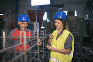Male and female worker wearing hard hats working on rebar in factory - JASF02064