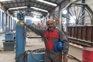 Portrait of confident worker standing next to a compressor in factory - JASF02067