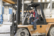 Tired worker sitting on forklift in factory - JASF02070