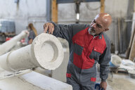 Worker in factory checking the burrs of a molded cement cannon - JASF02073