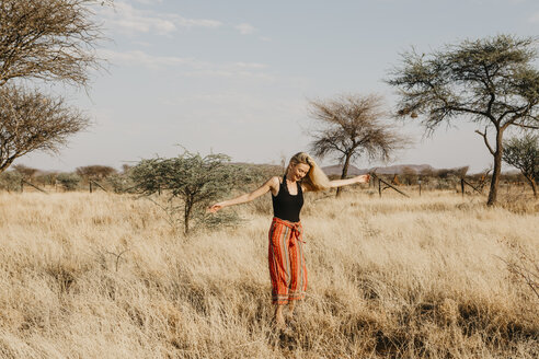 Africa, Namibia, blonde woman in grassland - LHPF00225