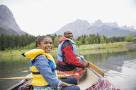 Father and daughter canoeing in lake - HEROF01710