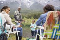 Family fishing at lakeside below mountains - HEROF01719