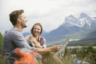 Couple looking at map in grass near mountains - HEROF01734