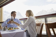 Couple toasting wine glasses at table on balcony - HEROF01755