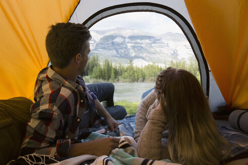 Couple laying in tent and looking at mountains - HEROF01776