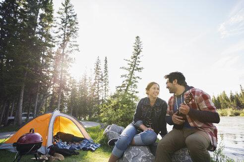 Couple playing ukulele at campsite - HEROF01782