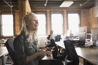 Businesswoman with cell phone laughing in office - HEROF01785