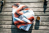 A blanket and coffee on a wooden deck in the morning sun - INGF11063
