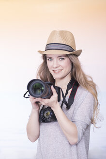 Portrait of smiling young woman comparing two different cameras - SKAF00082
