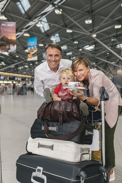 Portrait of happy family with baggage cart at the airport - MFF04716